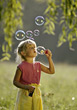 Blonde Girl Blowing Bubbles - stock photo