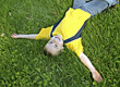 Playful Boy Laying in Grass with Arms Outstretched stock photo