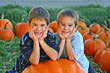 Children Boys Smiling Leaning on Huge Pumpkin stock photography
