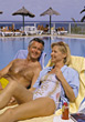 Couple lounging in chairs next to a pool at a resort