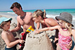 Family Building Sand Castle On The Beach - stock photography