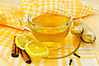 Ginger Tea In A Glass Cup, Two Slices Of Lemon, Cinnamon, Cloves, Ginger Root On A Yellow Napkin And A Wooden Board - stock photo
