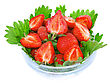 Close Heap Of Fresh Strawberries In Glass Bowl On Green Foliage . Isolated stock photography