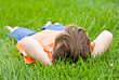Close Little Boy Laying in Grass stock photo