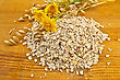 Oatmeal With Yellow Wild Flowers And Stalks Of Oats Against A Wooden Board stock image