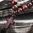 Rosary With A Wooden Cross Lying On Open Bible stock photo