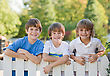 Stock Photo : Smiling Stock Image: Three Boys on a White Picket Fence