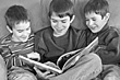 Three Brothers Reading Together stock image