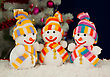 Stock Photo : Small Stock Photo: Three Snowmen In Front Of The Decorated White Evergreen Tree Over The Blue Background