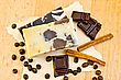 Two Bars Of Homemade Soap, Chocolate, Cinnamon, Coffee Beans On Old Paper On The Background Of Wooden Boards - stock image