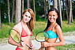 Two Girls Posing With Badminton Rackets On The Beach stock photography
