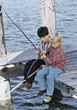 Two Young Boys Fishing From The Dock